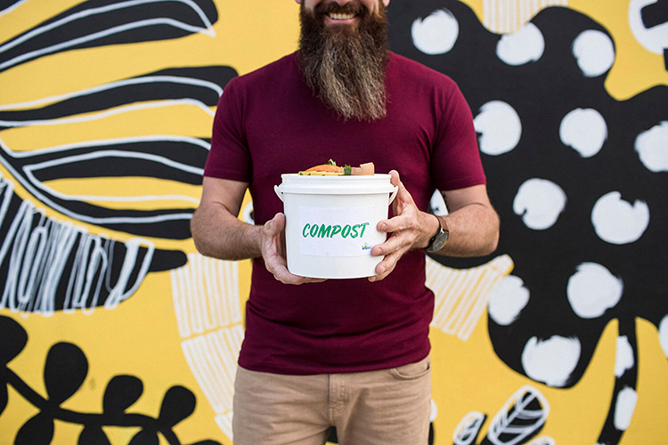 Man holding a bucket of scraps labeled compost