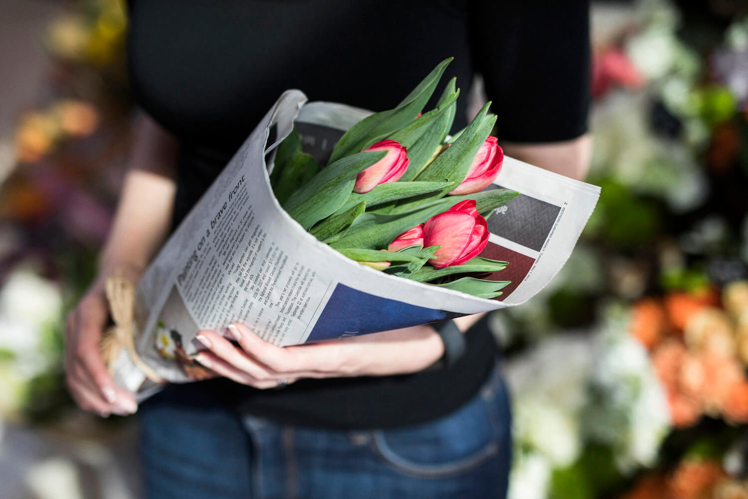 Lady holding flowers wrapped in newspaper